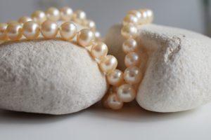 Piękne perły leżące na dwóch jasnych kamykach